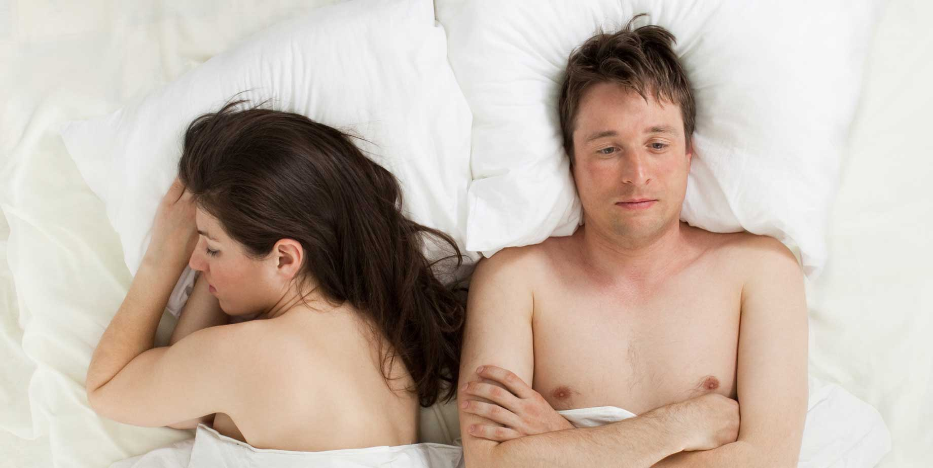 unhappy man in bed with woman