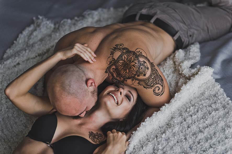 Happy young couple in underwear having fun in bed.