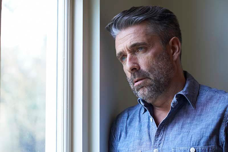 worried middle aged man at window